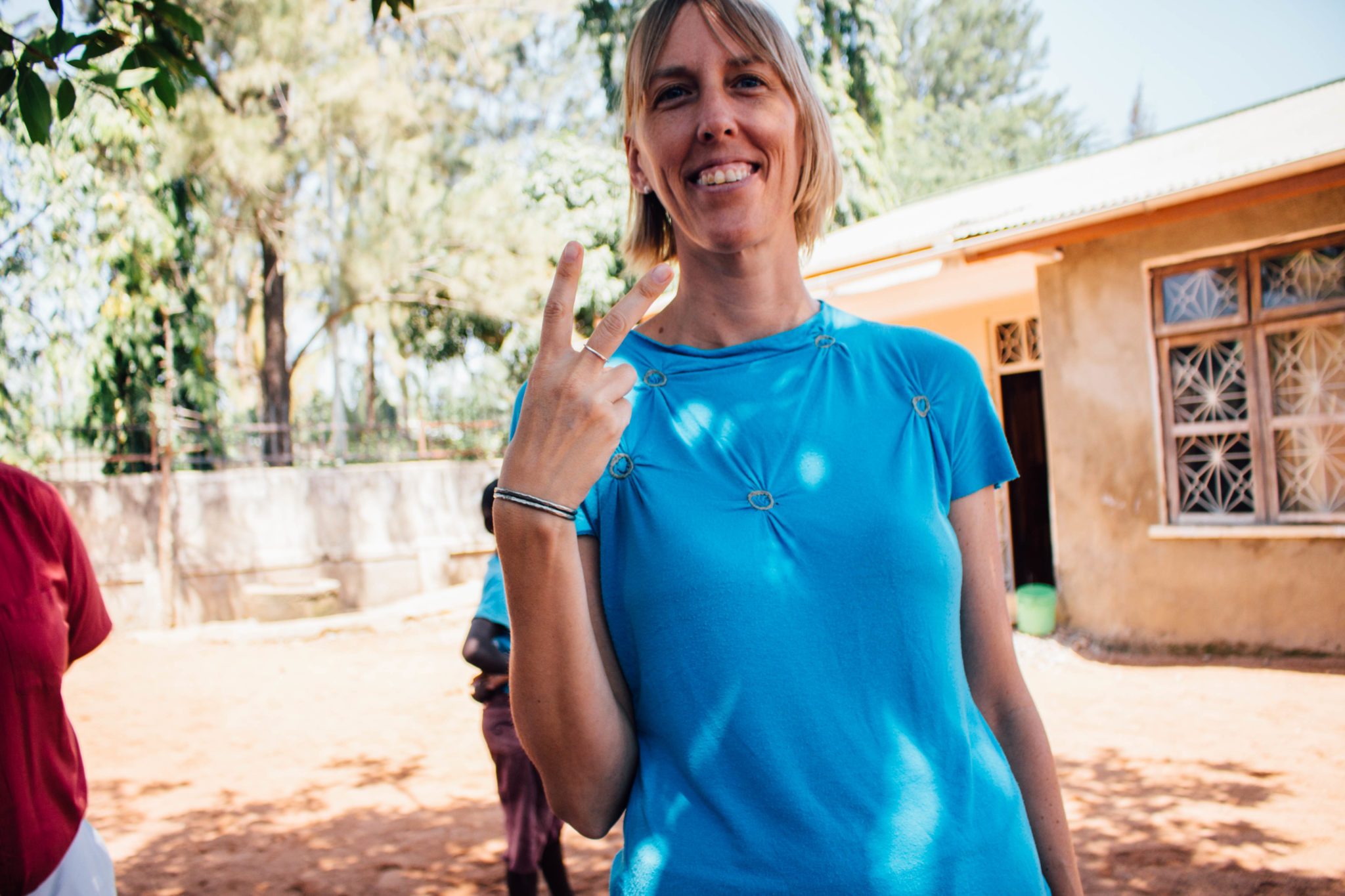 Associate professor Dr. Natalie Bourdon uses her fingers to make a peace sign in Tanzania.