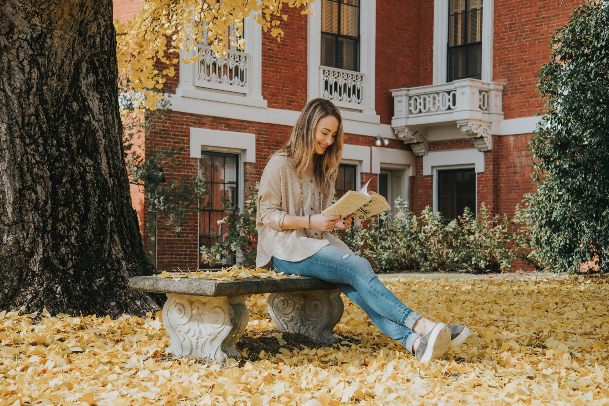 A student sits reading a book outside the Hay House.