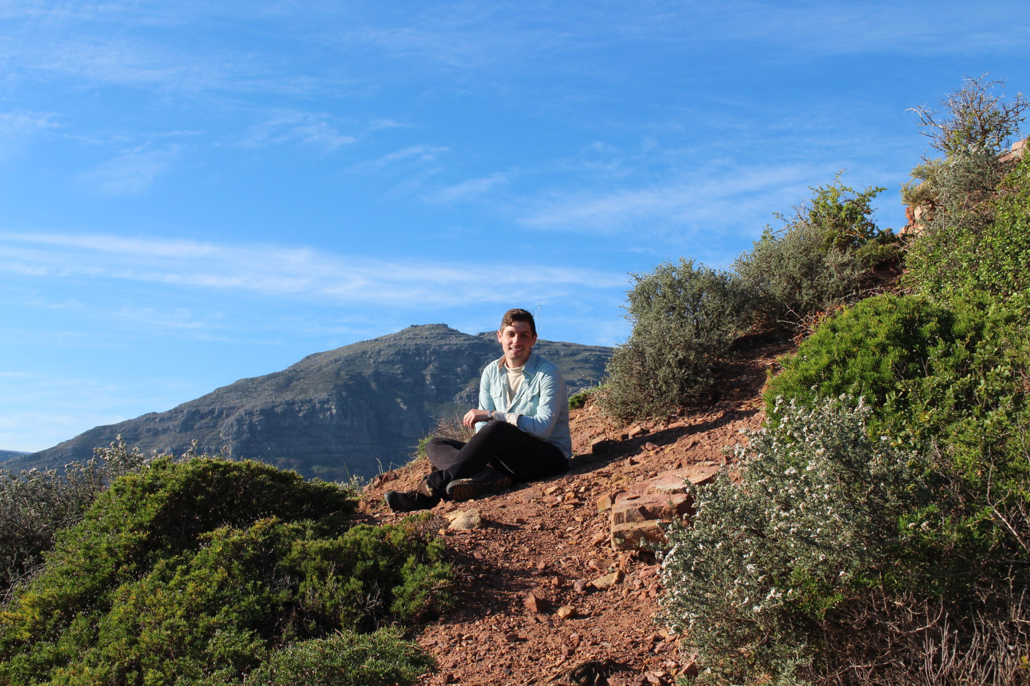 A Mercer student sits on a mountain in Africa.
