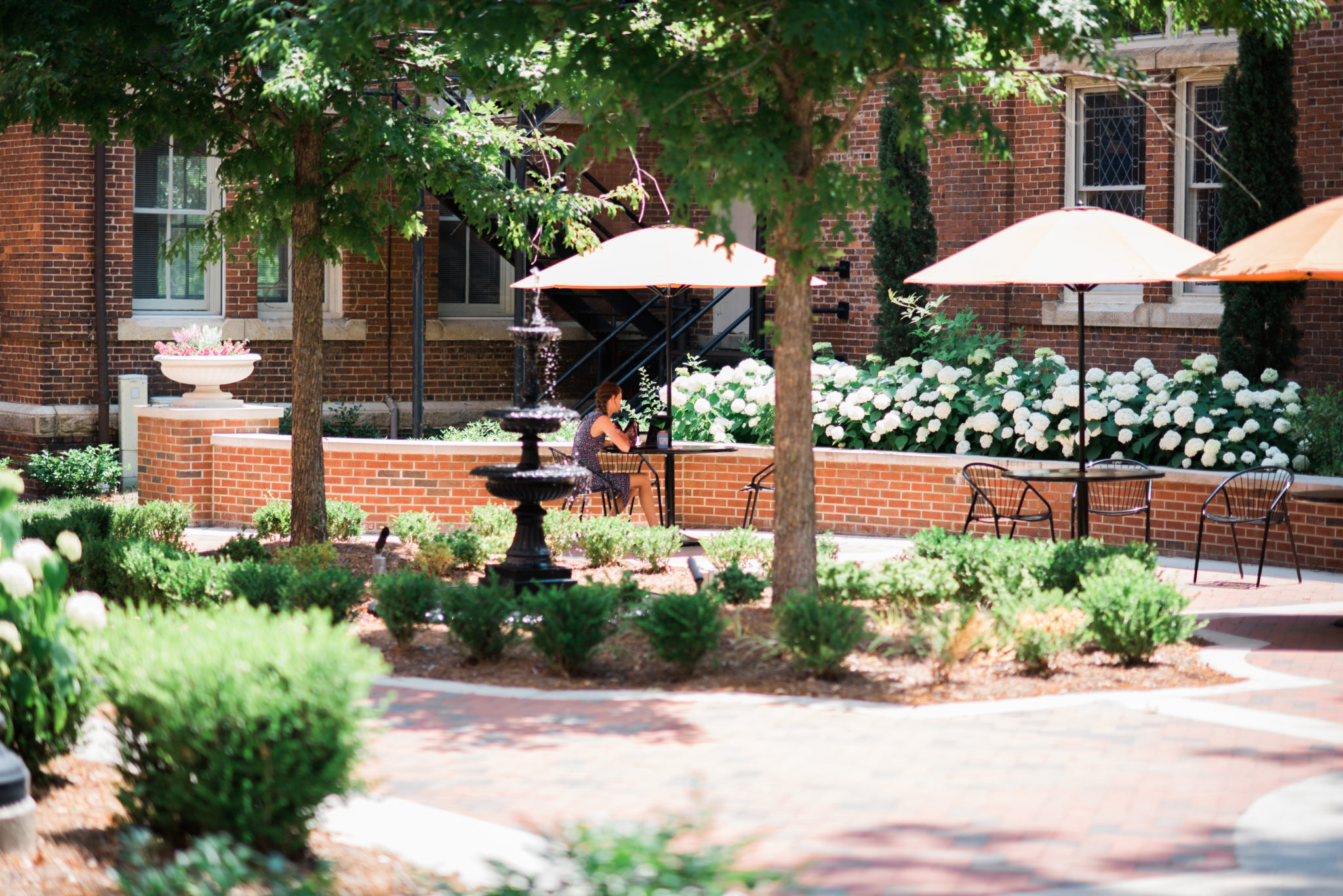 A student sits at a table in the Willingham courtyard