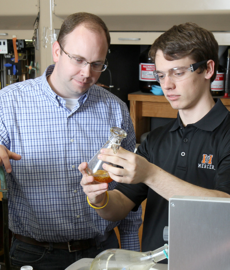 A professor and a student look at a beaker in a Chemistry lab.