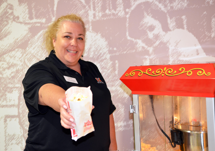 A woman holds out a bag of popcorn