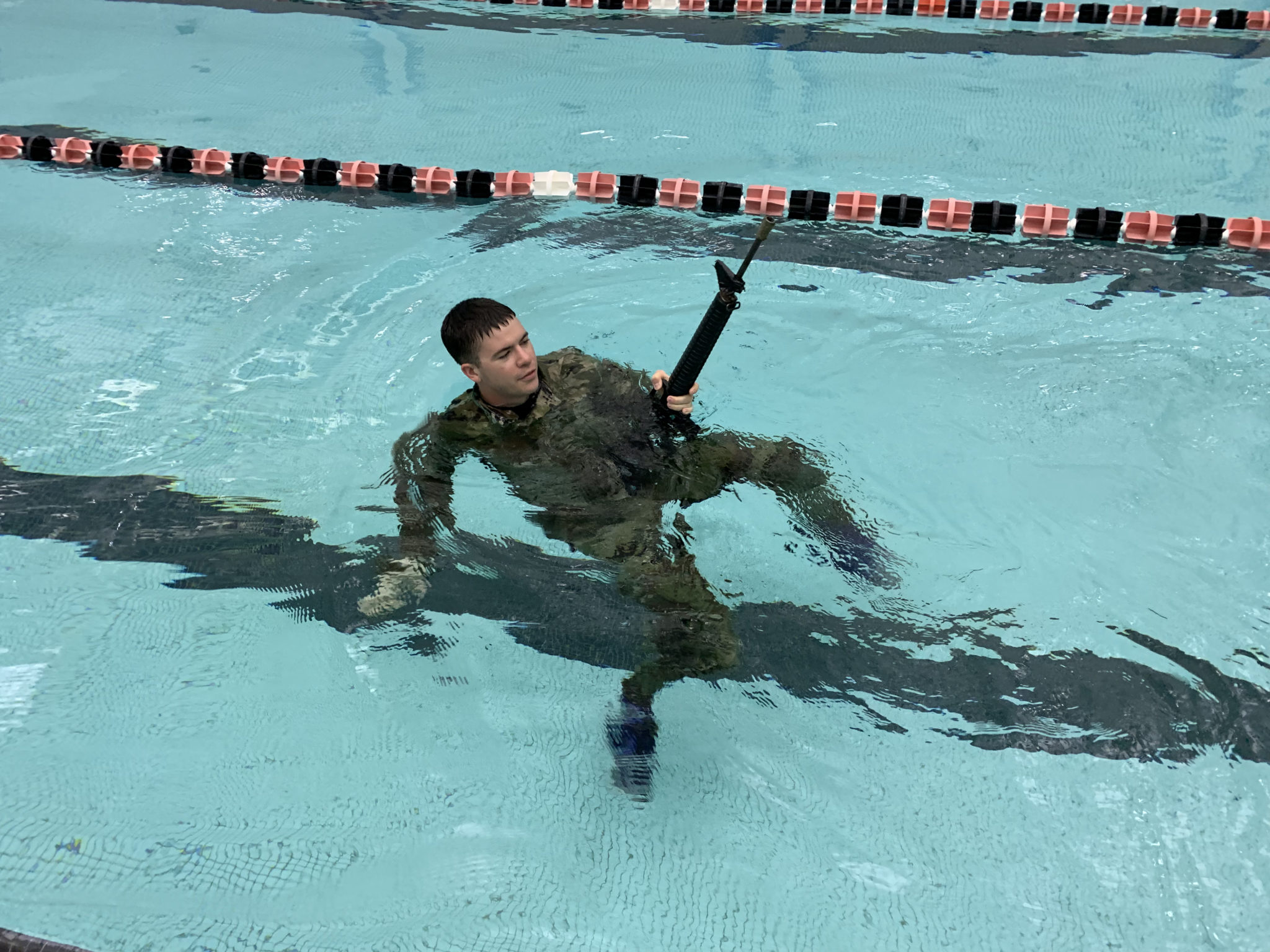 An ROTC cadet clothed in camo is in a pool