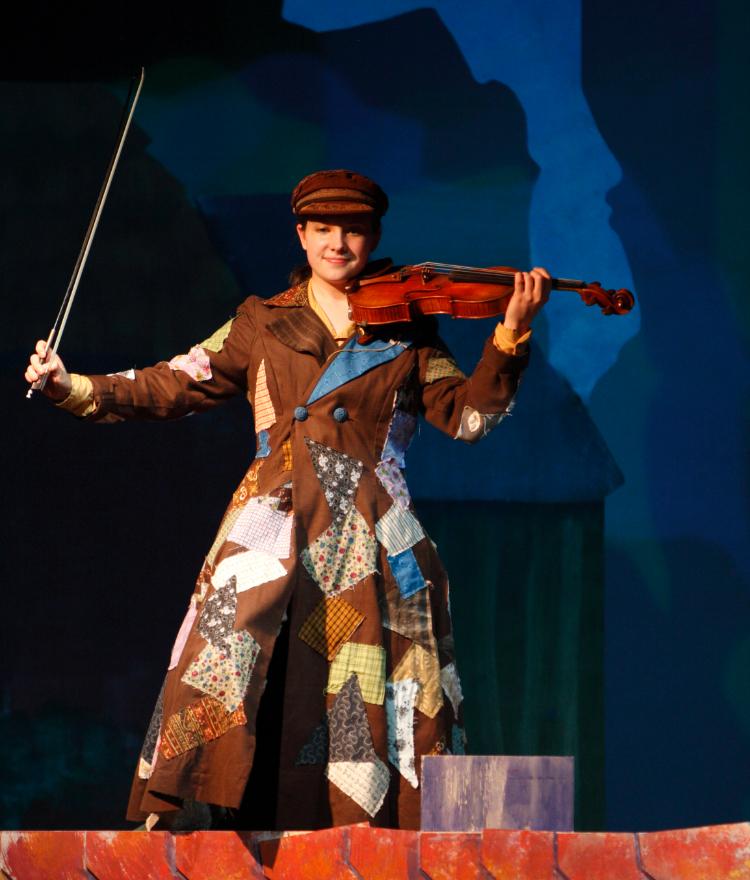 A Mercer theatre cast member holds a violin