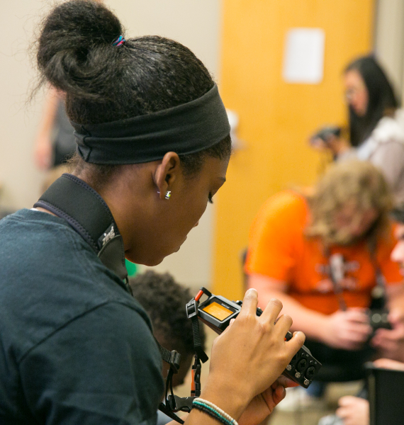A student examines an audio recorder