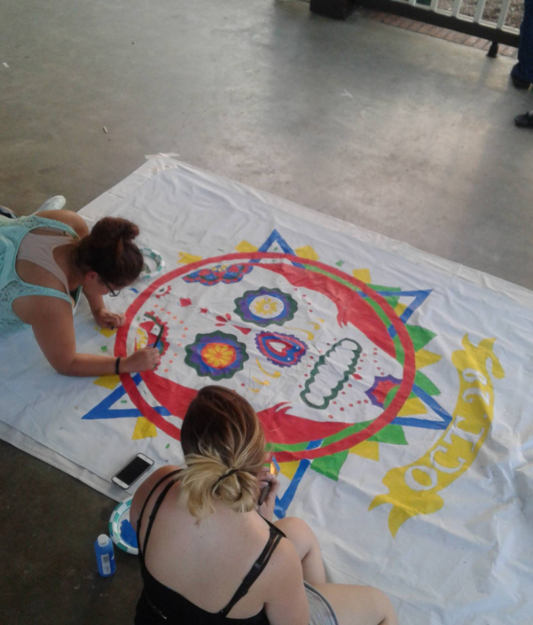 two students paint a decorated calavera on a white sheet