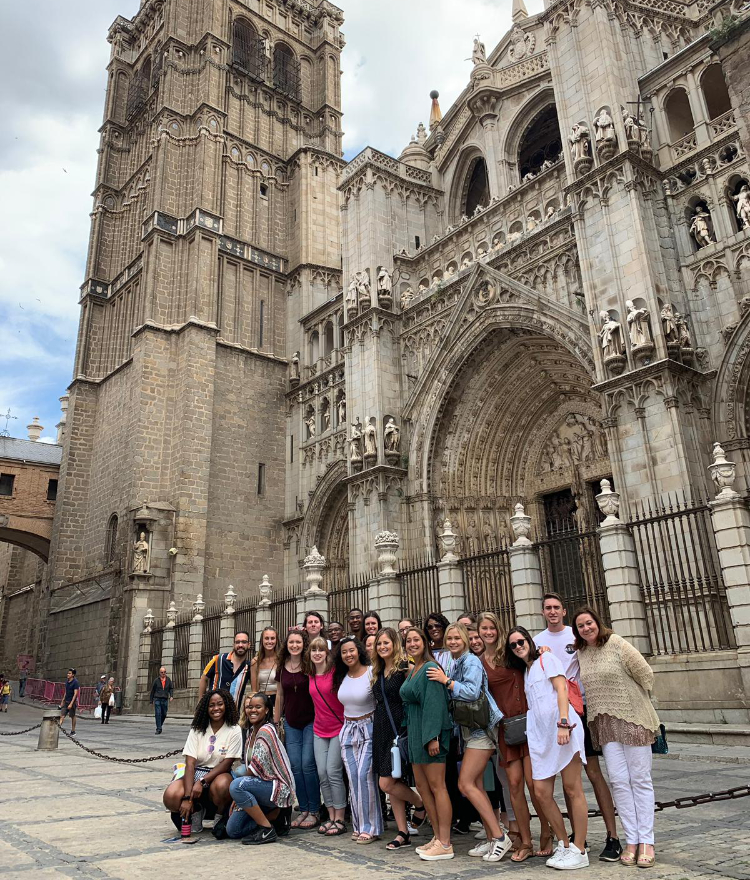 a group of students stand in front of a cathedral in seville