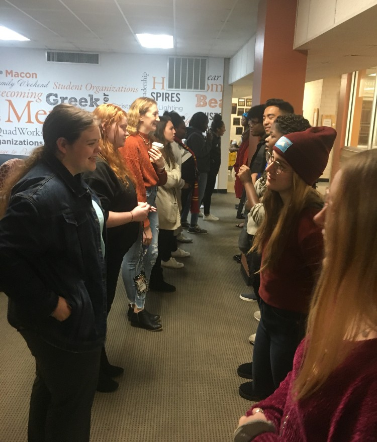 Students stand in two lines talking in pairs